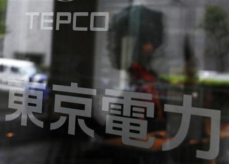 A woman walking into TEPCO headquarters building is reflected in the entrance door in Tokyo