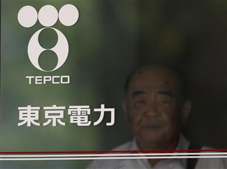 A man walking out is seen past Tokyo Electric Power Co's logo at the company headquarters in Tokyo