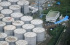 An aerial view shows workers wearing protective suits and masks working atop contaminated water storage tanks at TEPCO's tsunami-crippled Fukushima Daiichi nuclear power plant in Fukushima