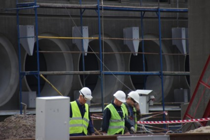 Workers pass in front of the concrete bunker where the dry casks will be stored horizontally.